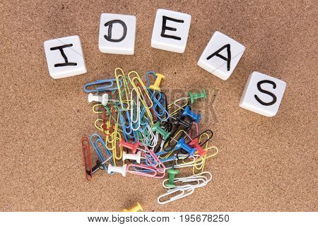 Background image with the word ideas with paperclips and board pins