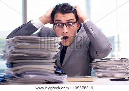 Busy angry businessman with heaps of paper