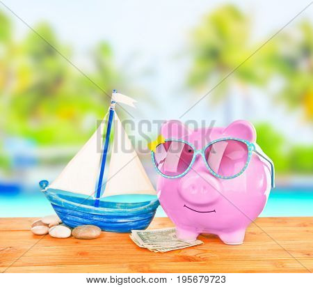 Piggy bank with sunglasses and money on wooden table against landscape background. Concept of money for vacation