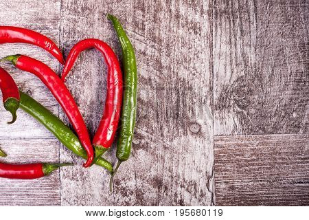 Spicy pepper on wooden background. Over top view. Chilli and hot
