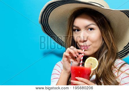Happy young woman drinking smoothie on a solid color background