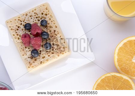 Crumpet topped with fruit on a white plate with orange juice and an orange cut in half