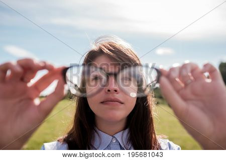 Young beautiful girl in shirt with long hair looks through glasses. The illusion of a large size.