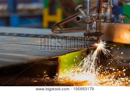 Acetylene torch semi auto machine cutting metalwork fabrication with bright sparks in factory.