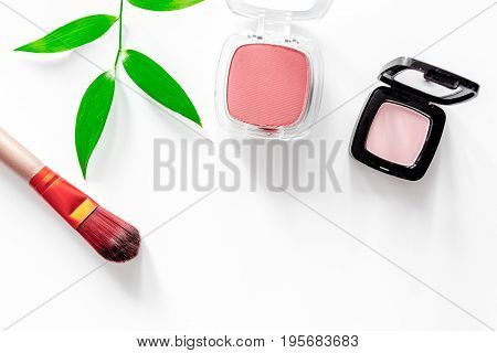Eyeshadow on white table background top view.