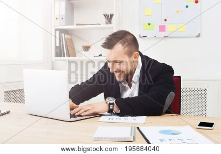 Excited businessman in office typing, addicted to computer. Happy man looks at laptop screen, internet leisure at work