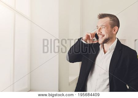 Business negotiations. Businessman talking by mobile phone, standing in modern office while looking in window