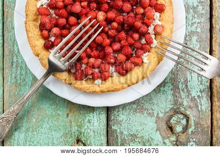 Forest strawberry and cottage cheese tart with vintage melchior forks on old turquoise table overhead view