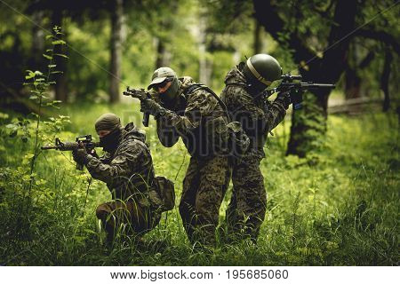 Strikeball players in camouflage with machine guns in woods among trees