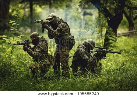 Soldiers in camouflage with machine guns in forest among trees