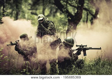 Officers in camouflage with machine guns amid smoke in forest