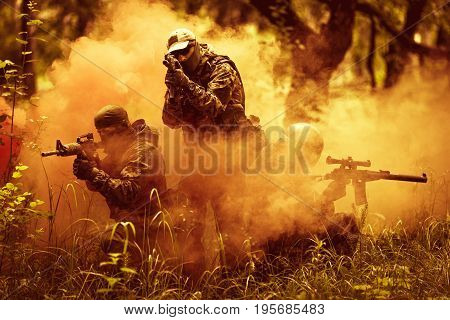 Officers in camouflage with machine guns on fire amidst smoke in forest
