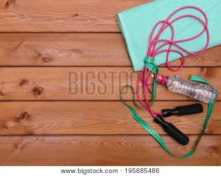 Fitness concept with towel bottle of water measure tape and skipping rope on wooden table background