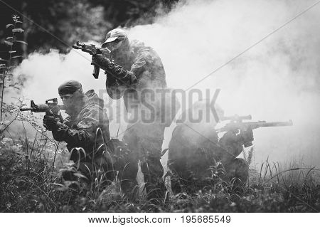 Soldiers in camouflage with machine guns on fire amidst smoke in forest. Black and white photo