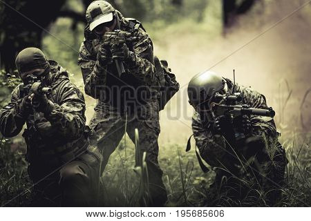 Strikeball players in helmets, with submachine guns in middle of smoky forest
