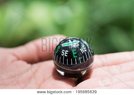 Hand holding a black compass using as an exploration adventure journey travel and discovery concept.