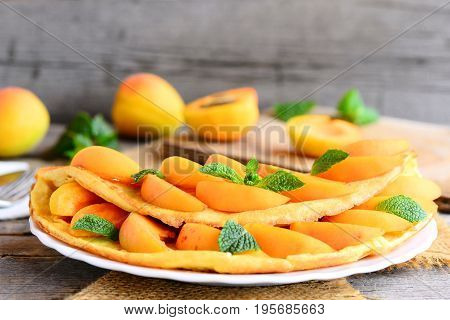 Sweet omelette with apricots. Homemade fried omelette with fresh apricots on a white plate and vintage wooden background. Delicious summer breakfast. Closeup