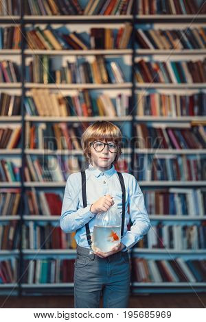 Little boy with goldfish in library