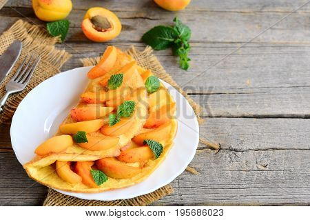 Fruit omelet. Veggie stuffed omelet with fresh apricots on a white plate and an old wooden background with copy space for text. Healthy egg breakfast recipe