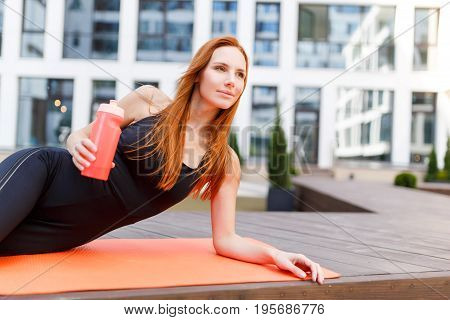 Model does exercises on rug in street against background of modern building