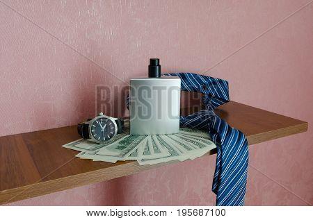 Gentleman concept. Clock dollars necktie and bottle of perfume on the shelf