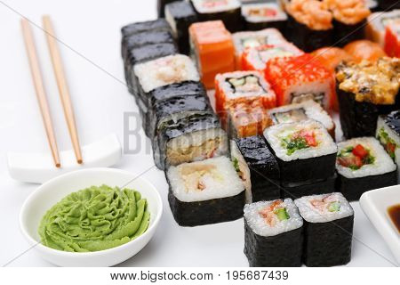 Japanese food restaurant. Sushi set on white background with wasabi bowl and chopsticks, closeup