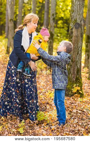 Family, nature, autumn and people concept - Portrait of Happy mother, father, son and daughter in fall.