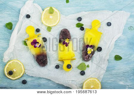 Homemade lemon blueberry ice cream with mint and edible flowers of garden viola on a turquoise summer background. Top View