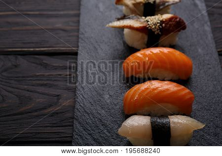 Sushi plate. Japanese food restaurant, eel, salmon and snapper sushi closeup on dark background. Pov with copy space on black wood