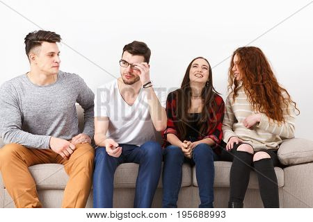 Young happy people communication, friends talking, having fun, sitting on couch indoors and laughing