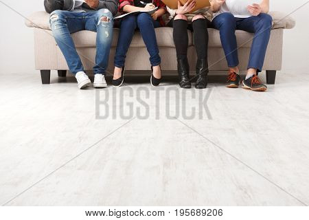 Unrecognizable young students preparing for exam, sitting on sofa in living room and studying, studio shot, copy space