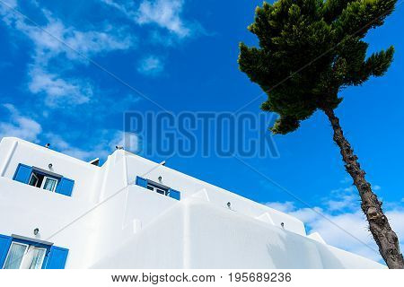 Whitewashed house with blue window shutters against bright blue Aegean sky
