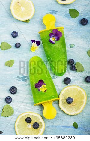 Mint ice ice cream with lemon juice and edible flowers of garden viola on a turquoise summer background. Top View