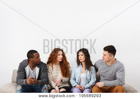 Happy multiethnic friends, casual people with copy space, sitting on couch indoors and laughing