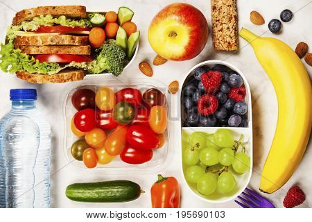 Healthy lunch box with sandwich and fresh vegetables, bottle of water and fruits on wooden background. Top view