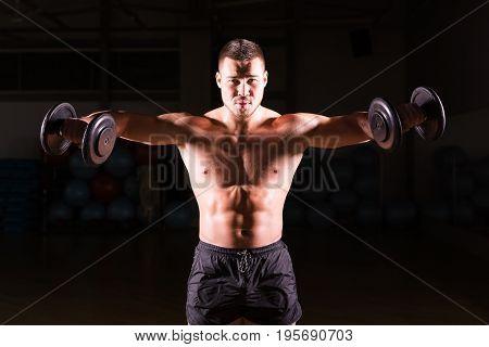 Muscular bodybuilder guy doing exercises with dumbbells over black background