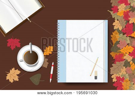 Cup of coffee part of an open book and a blank notepad ready for your text are lying on a brown wooden table. The edge forms colorful autumn leaves.