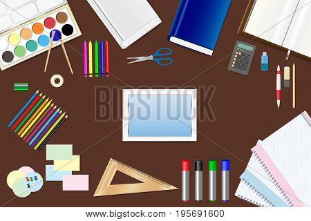 School supplies tablet with empty screen and tools are lying on a brown wooden table.