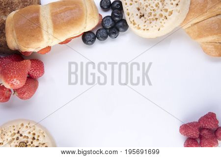 Background image of a variety if breakfast food including crumpets, toast, brioche buns and fruit