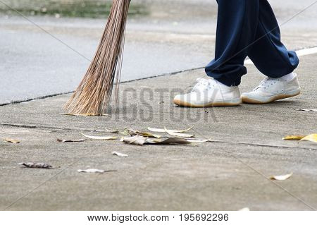 Student sweeping dried leafs on the floor in school.