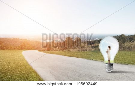 Young businesswoman trapped inside of light bulb on road