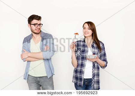 Couple in casual at white isolated background. Happy woman eating healthy food from take away box and man looking at it with disgust