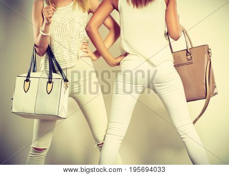 Fashion concept. Two slim women wearing white clothing with leather bags handbags.