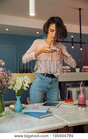 Pretty young girl blogger taking a photo with mobile phone while standing at the table in a cafe