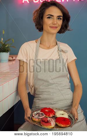 Portrait of a pretty young waitress in apron serving donuts on a tray in a caffeteria and looking at camera