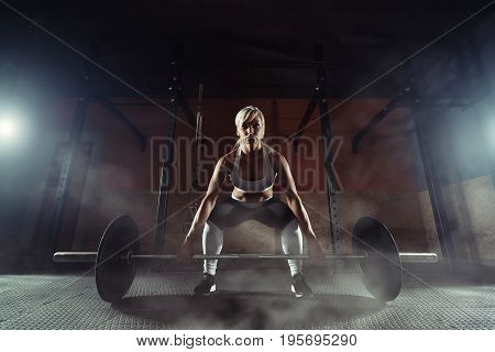 Muscular young fitness woman lifting a weight in the gym. Fitness woman deadlift barbell. Fitness woman.