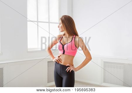 Beautiful fitness girl posing standing at window. Portrait of confident sporty woman with perfect body, healthy lifestyle and bodycare concept