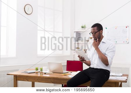 Pensive african-american businessman in office, reading news on tablet