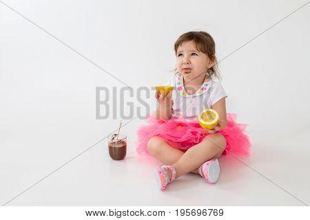 Photo of little children girl sitting over white background. Looking aside while eating chocolate dessert with lemon.