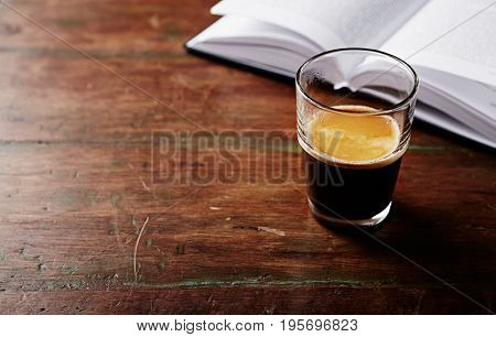 Glass of Espresso and a Book on an old Wooden Table